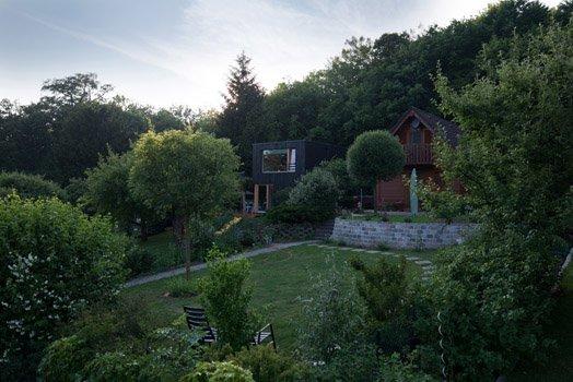 Современный черный дачный домик разительно отличается от соседних в садовом обществе.