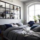 Со стороны спальни большое окно в изголовье кровати служит необычным элементом декора украшенным чашками, рюмками и прочими кухонными принадлежностями.