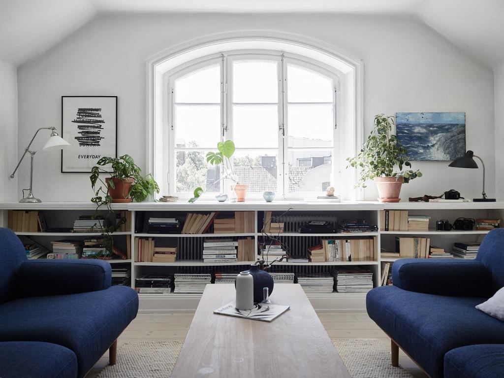 Полки под окном проходящие вдоль всей стены воспринимаются как широкий подоконник и вмещают массу книг.