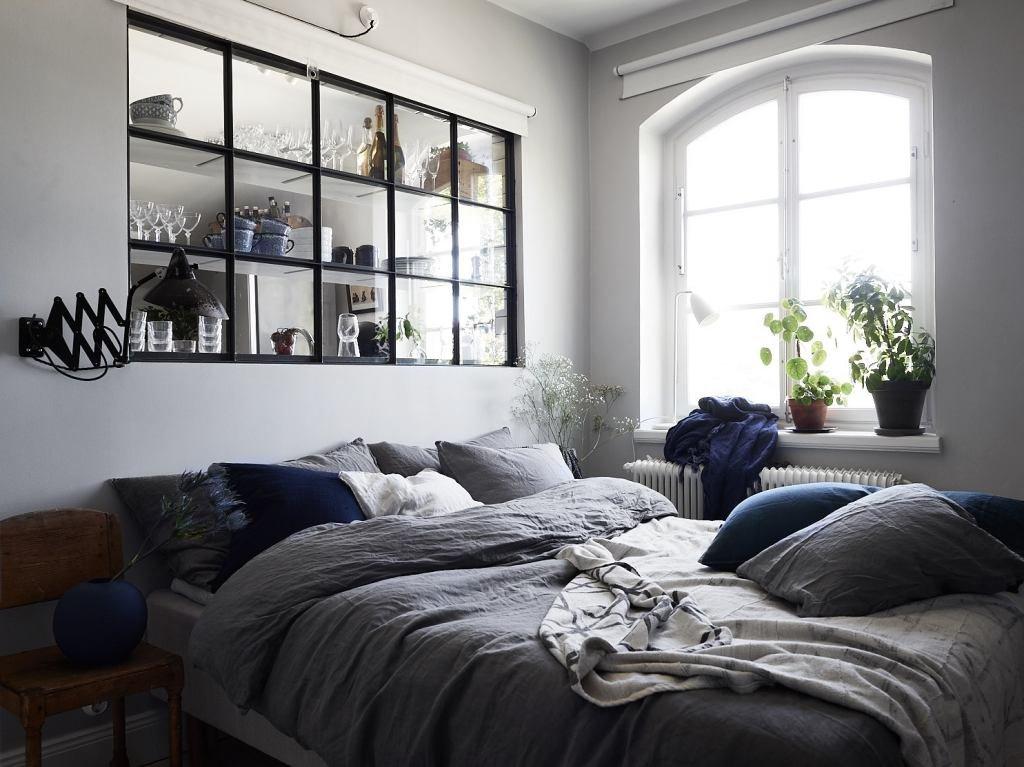 Со стороны спальни большое окно в изголовье кровати служит необычным элементом декора украшенным чашками, рюмками и прочими кухонными принадлежностями