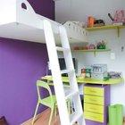 Кровать подвешенная на высоте в полтора метра позволила разместить в этой детской площадью 8 квадратных метра рабочий стол школьника, а также место для чтения и отдыха. Акцентная фиолетовая стена служит фоном для яркой мебели.