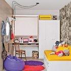 Яркая детская для подростка. Кровать вместе с креслом-мешком выступают в роли маленькой гостиной для встречи с друзьями. В то время как стена у окна занята плательным шкафом и рабочим столом у окна.