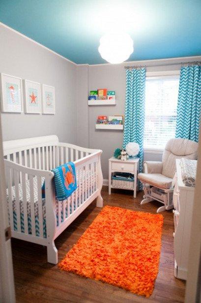 Детская с морской тематикой в интерьере поданной несколько необычным образом. Цвет стен нейтрально серый, а потолок и шторы бирюзового цвета вместе с картинками над детской кроватью определяют тему оформления детской.