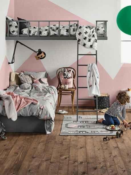 Если две кровати в двух уровнях расположены под углом и лишь частично перекрывают друг друга, пространство воспринимается как менее загроможденное. Необычные розовые горы на стенах оживляют интерьер, придают ему динамики.