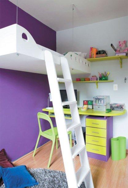 Кровать подвешенная на высоте в полтора метра позволила разместить в этой детской площадью 8 квадратных метра рабочий стол школьника, а также место для чтения и отдыха. Акцентная фиолетовая стена служит фоном для яркой мебели