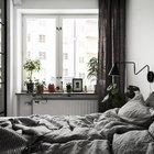 Как и по всей квартире, зеленые растения в спальне довершают образ живой квартиры несмотря на доминирующие белые и серые тона.