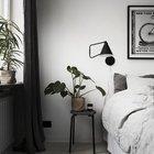 Стул или табурет не редкость в качестве замены прикроватной тумбочки. Реже на нем можно увидеть домашнее растение. Другой модный аксессуар - антикварный рекламный плакат на стене в изголовье кровати.