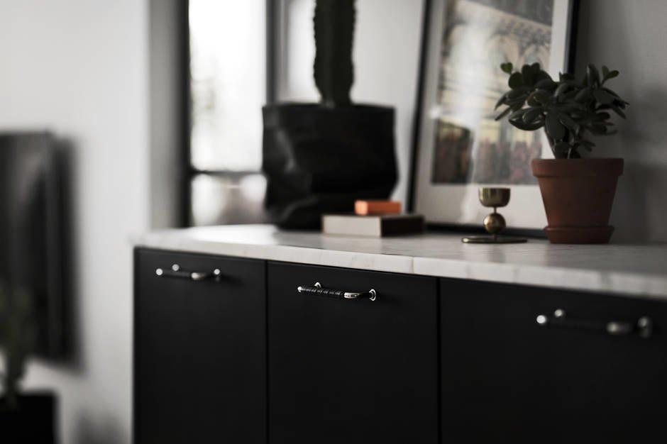 Фото, комнатные растения и декор на выступающей в гостиную части кухонной мебели подчеркивают, что это уже не кухня