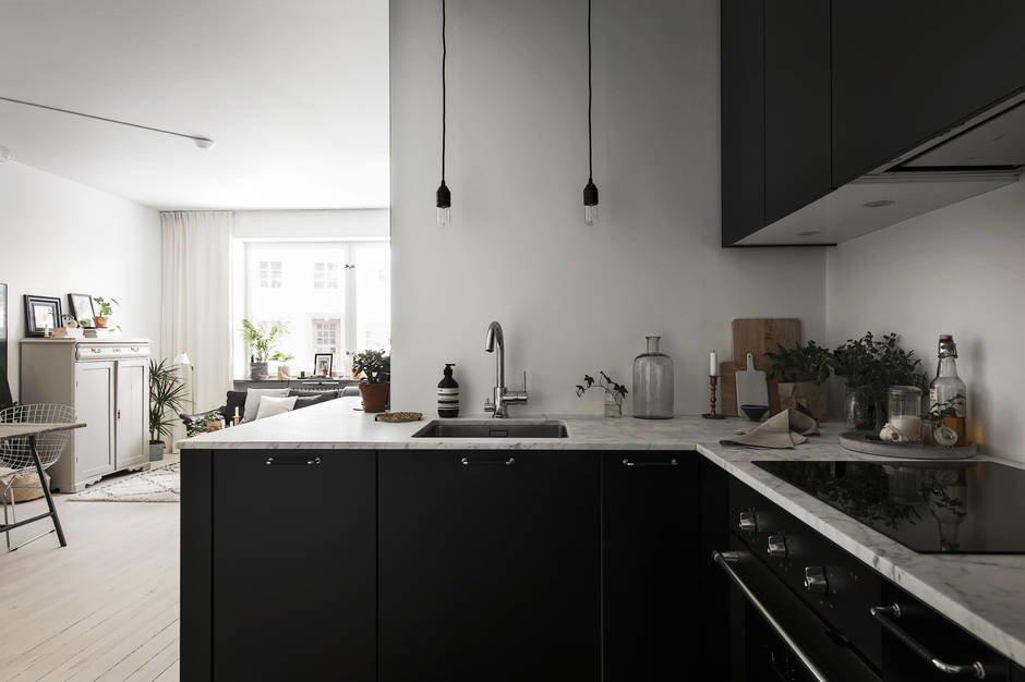 Необычные минималистские светильники в виде висящих черных патронов с лампочками скрадывают привычное ощущение утилитарности кухни.