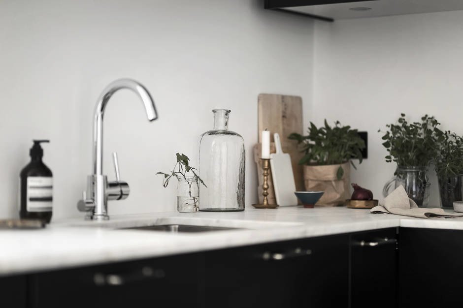 Поскольку кухня совмещена с гостиной и является проходной, то ее украшают подсвечники, антикварные бутылки
