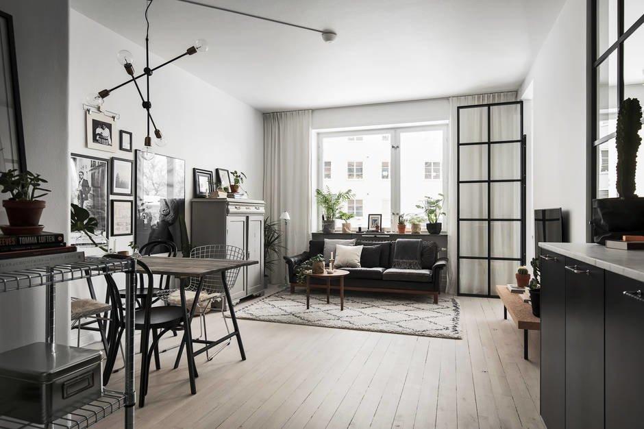 Шторы от потолка до пола визуально увеличивают окно. А стеклянные двери в спальню с изящной черной рамой не скрадывают пространства гостиной