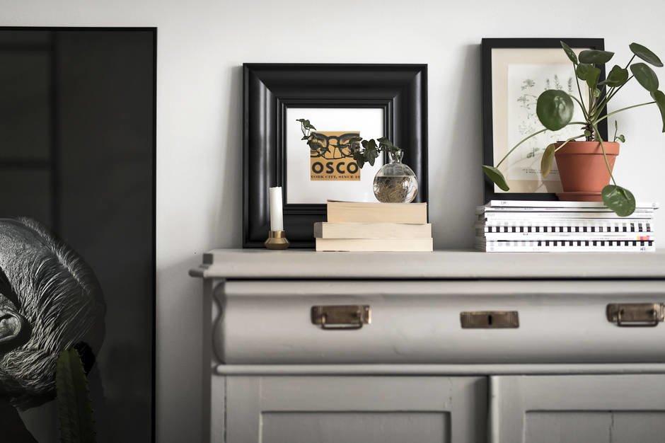 Светло-серый антикварный шкаф в гостиной. На шкафу достаточно места для размещения картин и декора.