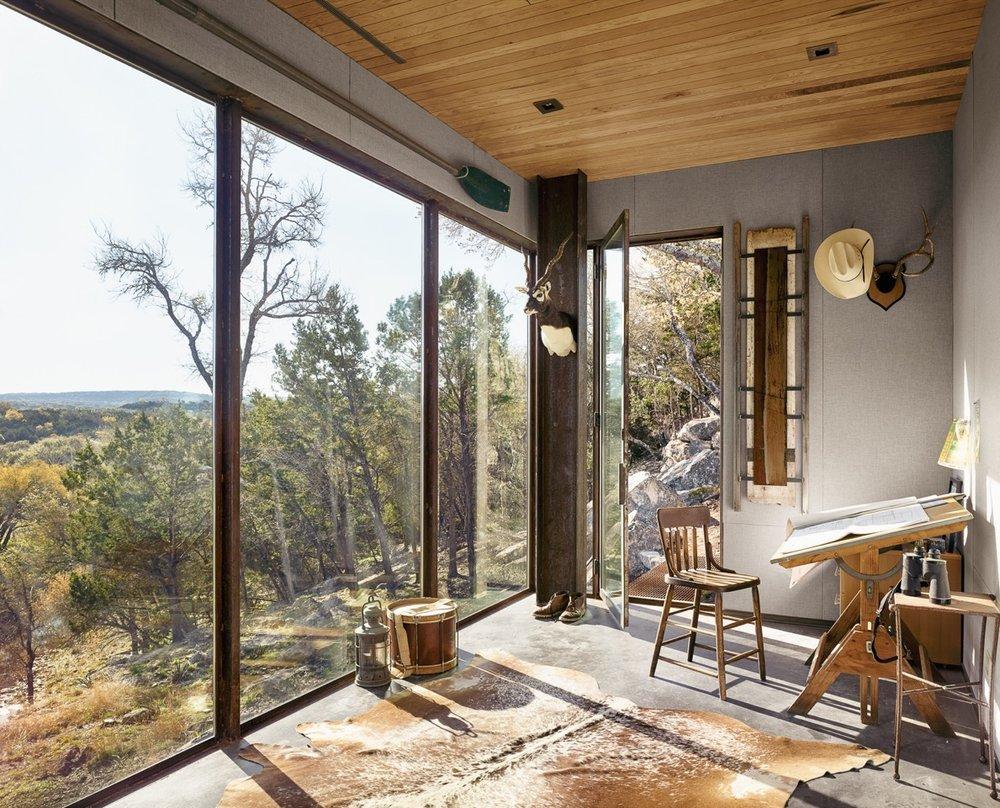 Большая комната с деревянным потолком и стеклянной стеной служит жилой комнаты. Стены комнаты украшены соответствующим назначению дома декором.
