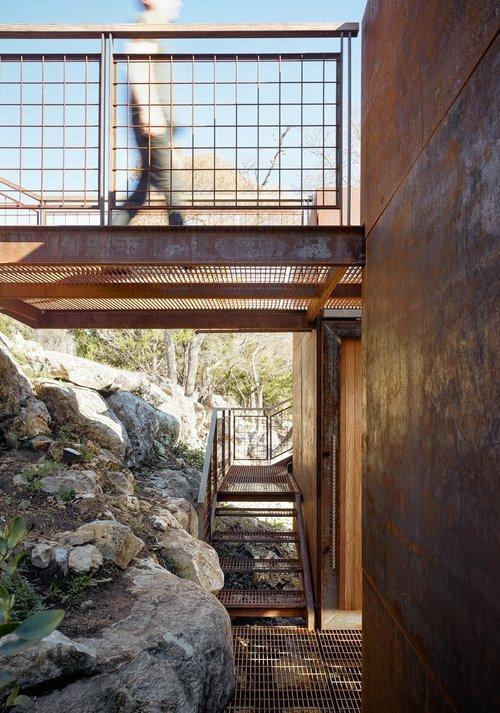 Между скалой и домом достаточно места для того чтоб пройти человеку, а выступающие камни только украшают крыльцо.