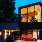 Эффектная подсветка дома подчеркивает его красоту и красоту машин владельца дома.
