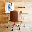 Минималистский домашний офис со стенами и полом отделанными стенами, кожаным креслом и стеклянным рабочим столом.