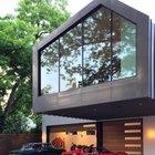 Нависающая спальня образует козырек над въездом в гараж. (архитектура,дизайн,экстерьер,современный,минимализм,фасад,гараж,парковка,сарай)