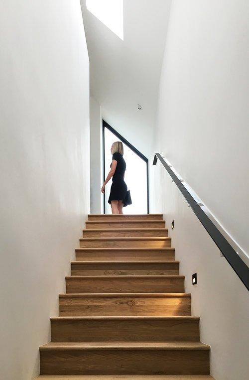 Деревянная лестница на второй этаж с подсветкой смонтированной в боковой стене. Днем лестница ярко освещена солнечным светом из окон в крыше.