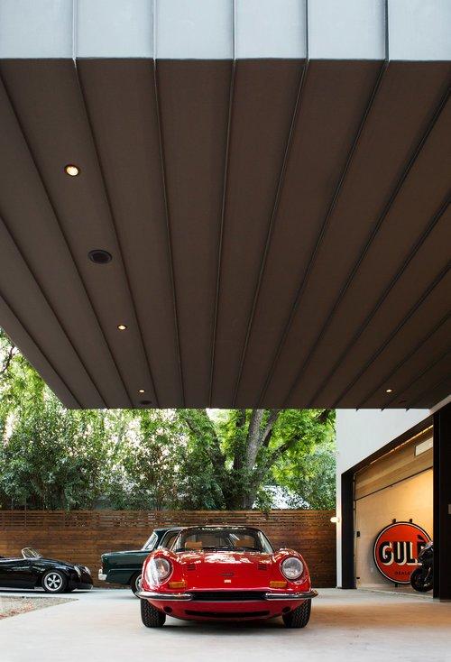 Дополнительная подсветка в перекрытии нависающей спальни превращают площадку под ней в выставочную витрину для любимой машины владельца дома.