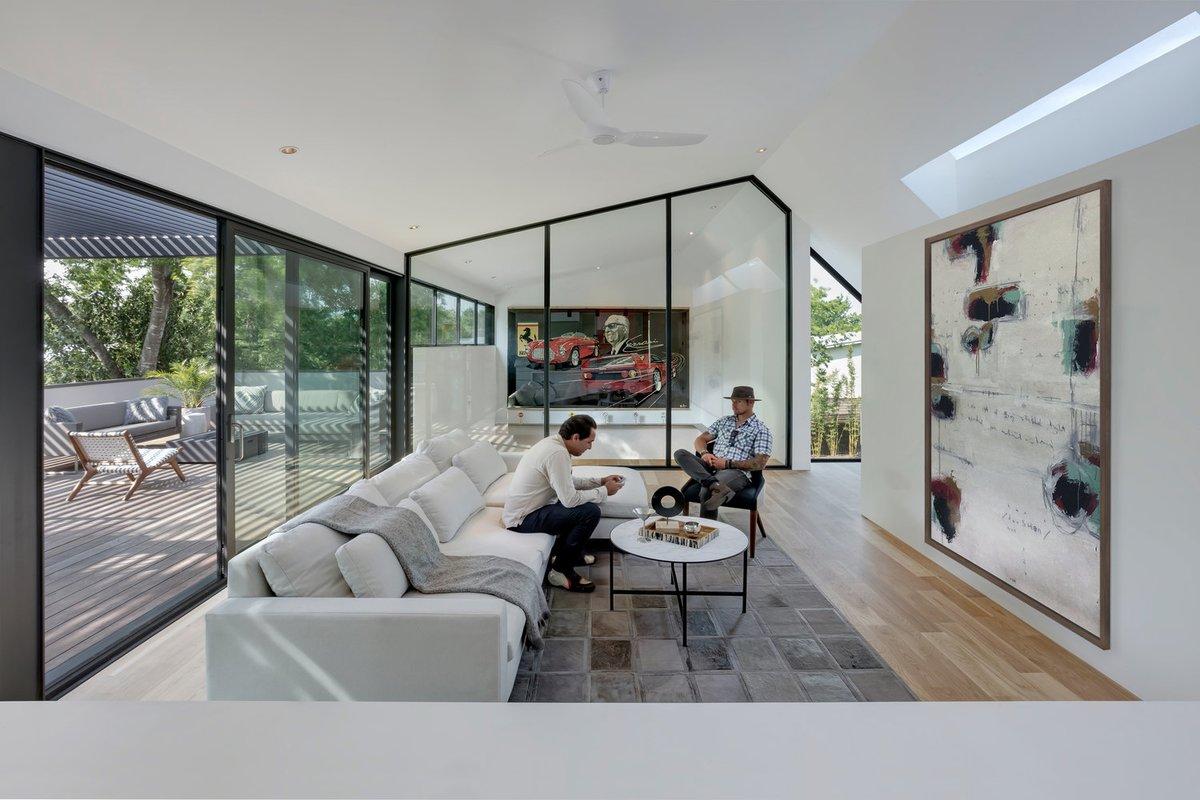 Гостиная на втором этаже с остекленной стеной выходящей на террасу, световым окном в крыше и вторым светом в гараж отделенным стеклянной перегородкой.