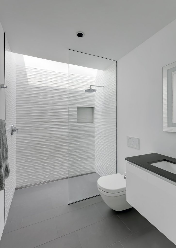 Минималистская белая ванная комната с окном над душем.