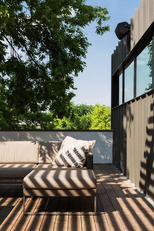 Терраса над гаражом покрыта комфортным деревянным настилом, меблирована садовой мебелью и является продолжением гостиной