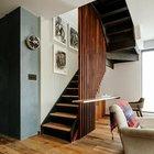 Лестница на второй этаж закрыта от жилой комнаты вертикальной решеткой из деревянного бруса.