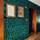 Напротив темно-серой бетонной стены, стена оклеенная зелеными обоями выглядит ярко и эффектно. Этому способствует ее сочетание с деревянной отделкой дверных проемов, латунные светильники и выключатели.
