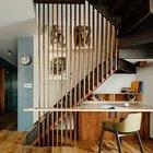 Под стальной лестницей на второй этаж квартиры удобно разместился рабочий стол.