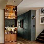 Шкаф-бар занимает всю высоту от пола до потолка, чтобы визуально вытянуть пространство вверх. В нижней части шкафа миски для собак.