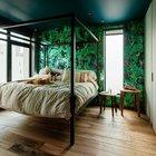 Темные зеленые тона и растительные орнаменты доминируют в отделке стен спален, что в сочетании с цветом натурального дерева создает расслабляющую атмосферу. Кровать из профильной трубы изготовлена на заказ.