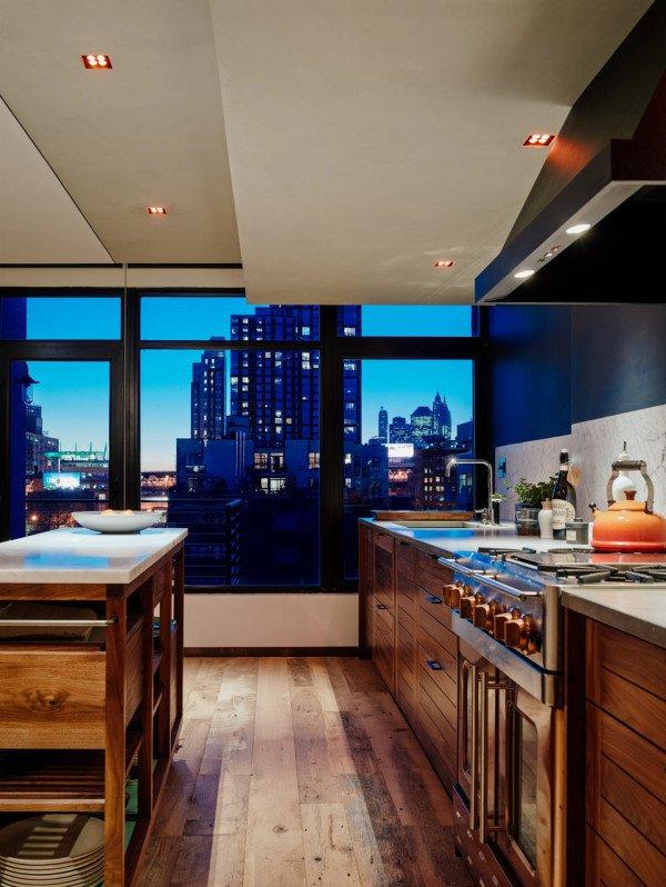 Деревянные фасады кухни выглядят современно, особенно на воне городского пейзажа за окном.