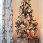 Елка на деревянном ящике в углу комнаты украшена лентами, шишками, серебряными и белыми шарами и елочными игрушками.
