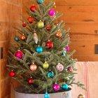 Елка в цинковом ведре украшенная яркими игрушками в деревянном доме.