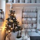 Крошечная елка в горшке на подносе украшает кухню. На елке серебристые шарики и светящаяся гирлянда.