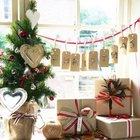 Маленькая елка на подоконнике украшенная бумажными сердечками и бантиками. Горшок декорирован мешковиной, а рядом на подоконнике подарочные коробки.