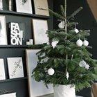Маленькая елка в горшке декорированном белой тканью украшена белыми и прозрачными елочными игрушками.