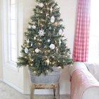 Маленькое дерево в цинковом ведре украшенное белыми украшениями, снежинками и гирляндами.