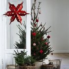 Скромная елка в корзине украшенная красными игрушками. У елки стоят корзинки поменьше с хвоей и шишками. Окно украшено рождественской звездой из красной бумаги. (маленькая елка,новый год,рождество,елка,подарки,декор,елочные игрушки,хвоя,гирлянды,конфети,сделай сам,самоделки,скандинавский,скандинавский интерьер,скандинавский стиль,французская провинция,прованс,стиль прованс,интерьер прованс)