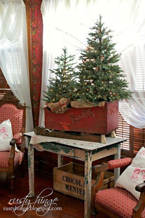 Две маленькие елочки в антикварных деревянных санках украшенные светящейся гирляндой.
