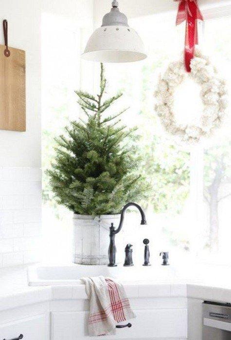 Элегантная елочка в деревянном ведерке украшает кухню, как и праздничный венок на окне.