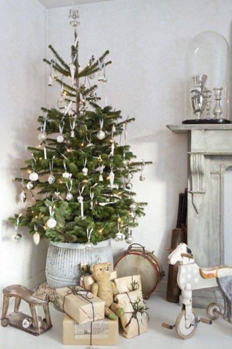Елка в высоком горшке и серебристыми украшениями. Деревянные игрушечные лошади у елки намекают на праздник детства.