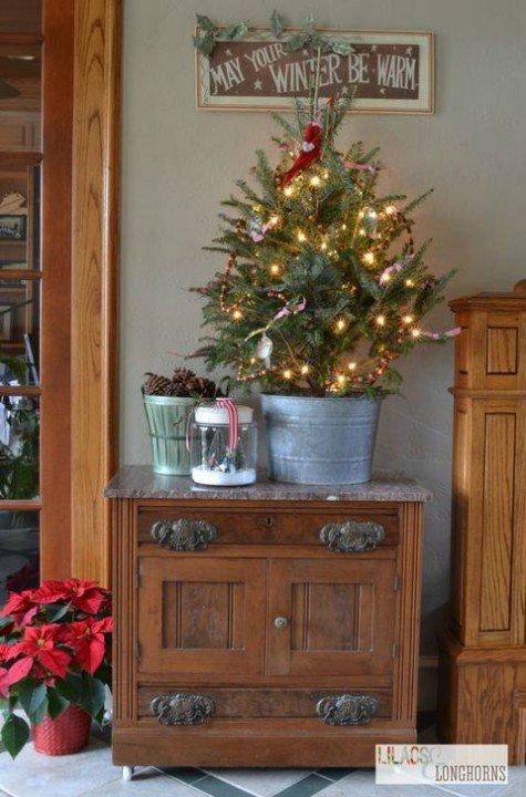 Еще одна небольшая елка в цинковом ведре украшенная новогодними огоньками.