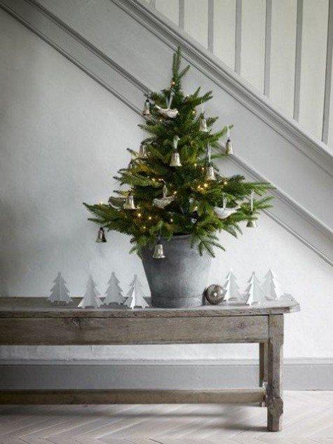 Крохотная елочка в ведре украшенная колокольчиками и птичками. На скамье под елкой целая выставка белых бумажных елочек.