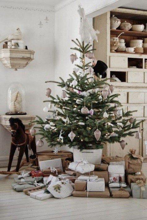 Маленькая ель украшенная металлическими игрушками и кучей подарков под елкой.