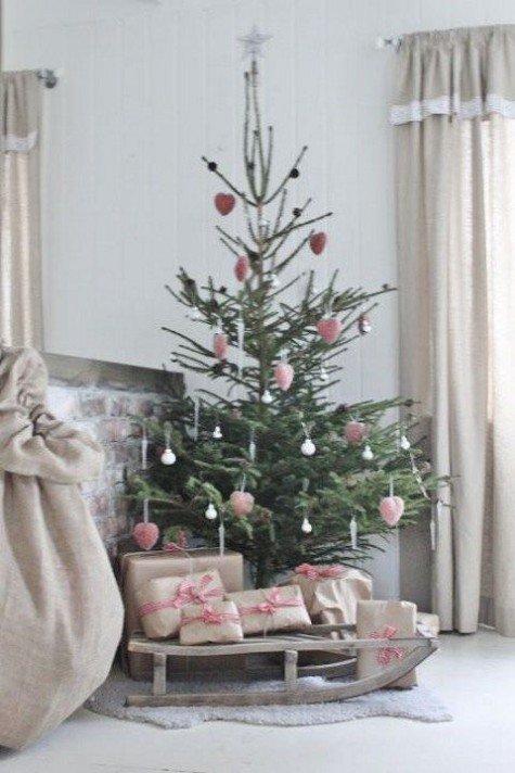 Маленькая ель украшенная розовыми игрушками, с подарочными коробками на санях под ней.