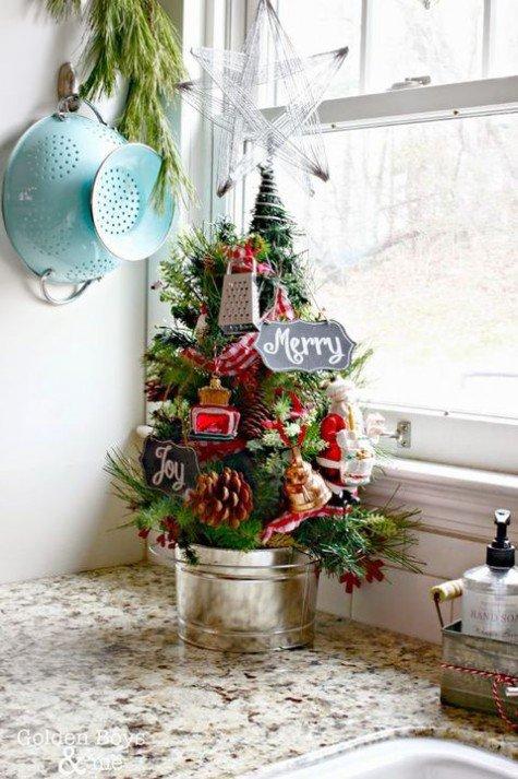 Маленькая елка украшающая кухню декорирована крохотными кухонными принадлежностями