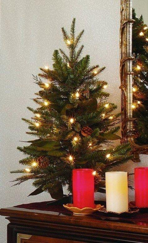 Маленькая елочка на столе украшенная шишками и огнями. Украшением служат и яркие цветные свечи на столе рядом с елкой.