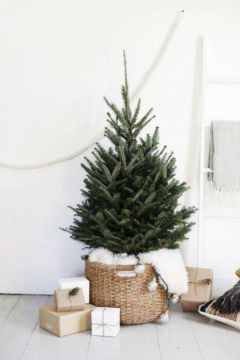Маленькая елочка в корзинке с мехом. Подарочные коробки у елки выступают в роли украшения.