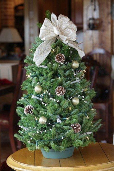 Маленькая пышная искусственная елочка украшенная шариками шишками и бантиком на верхушке.